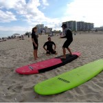 guy shows two people how to properly stand on a surfboard while on land