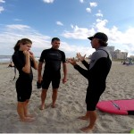 Guy talking to two people about surf instructions