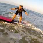 girl with tattoo learns to balance on surfboard