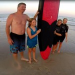 Family stands with surfboard on the beach to take picture