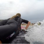 girl laying on surfboard as she gets ready to stand up on the board