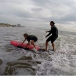 Instructor helping girl stand up on surfboard