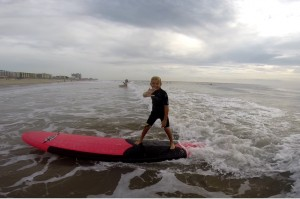 little boy waving to camera as he surfs
