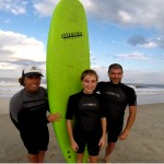 three people pose with green surfboard on the beach