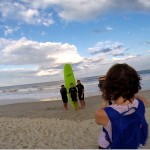 Woman taking a picture of 3 boys in front of green surfboard
