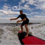 man surfing on red and black surfboard