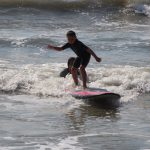 little boy surfing a wave with instructor helping behind