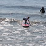 Little boy almost standing up on surfboard