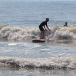 young man surfing several waves