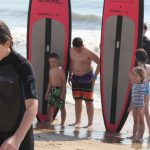 group of kids posing next to two surfboards