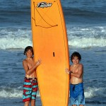 two young boys pose next to orange surfboard on beach