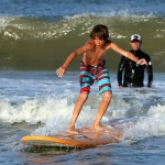 boy in striped bathing suit surfs a wave on orange surfboard