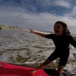 Girl surfing in shallow water looking at camera close up