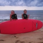 boy and girl pose next to surfboard with big smiles and cloudy skies in the back