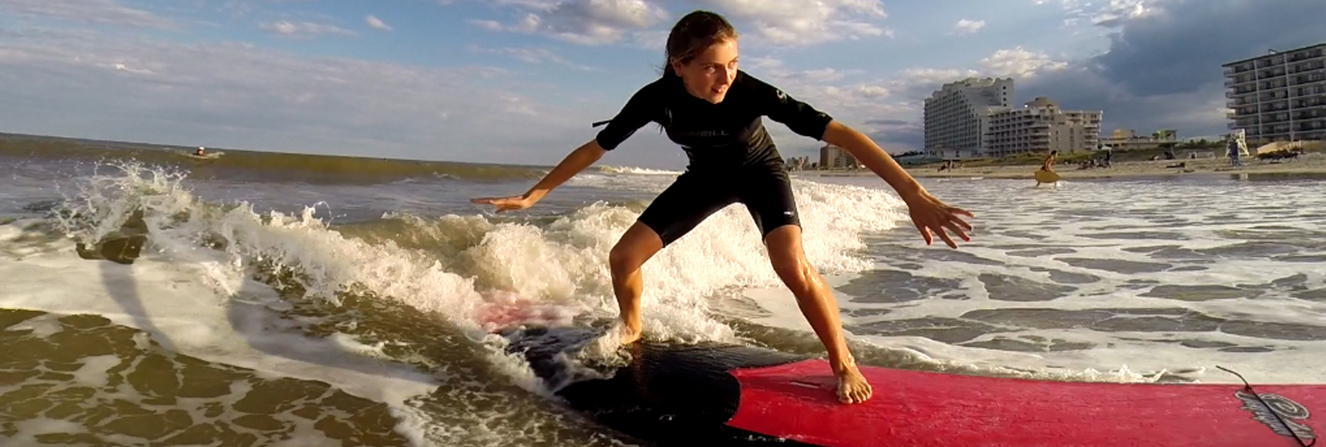 girl balances on red surfboard in black wetsuit