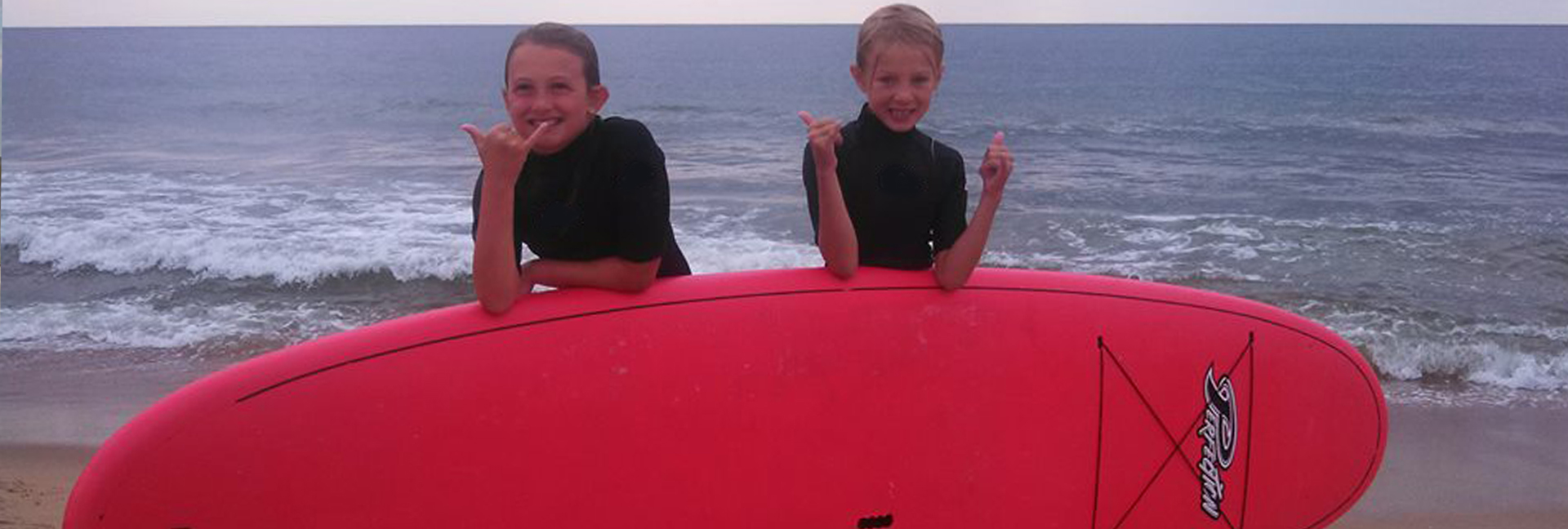 boy and girl pose behind a red surboard with a thumbs up